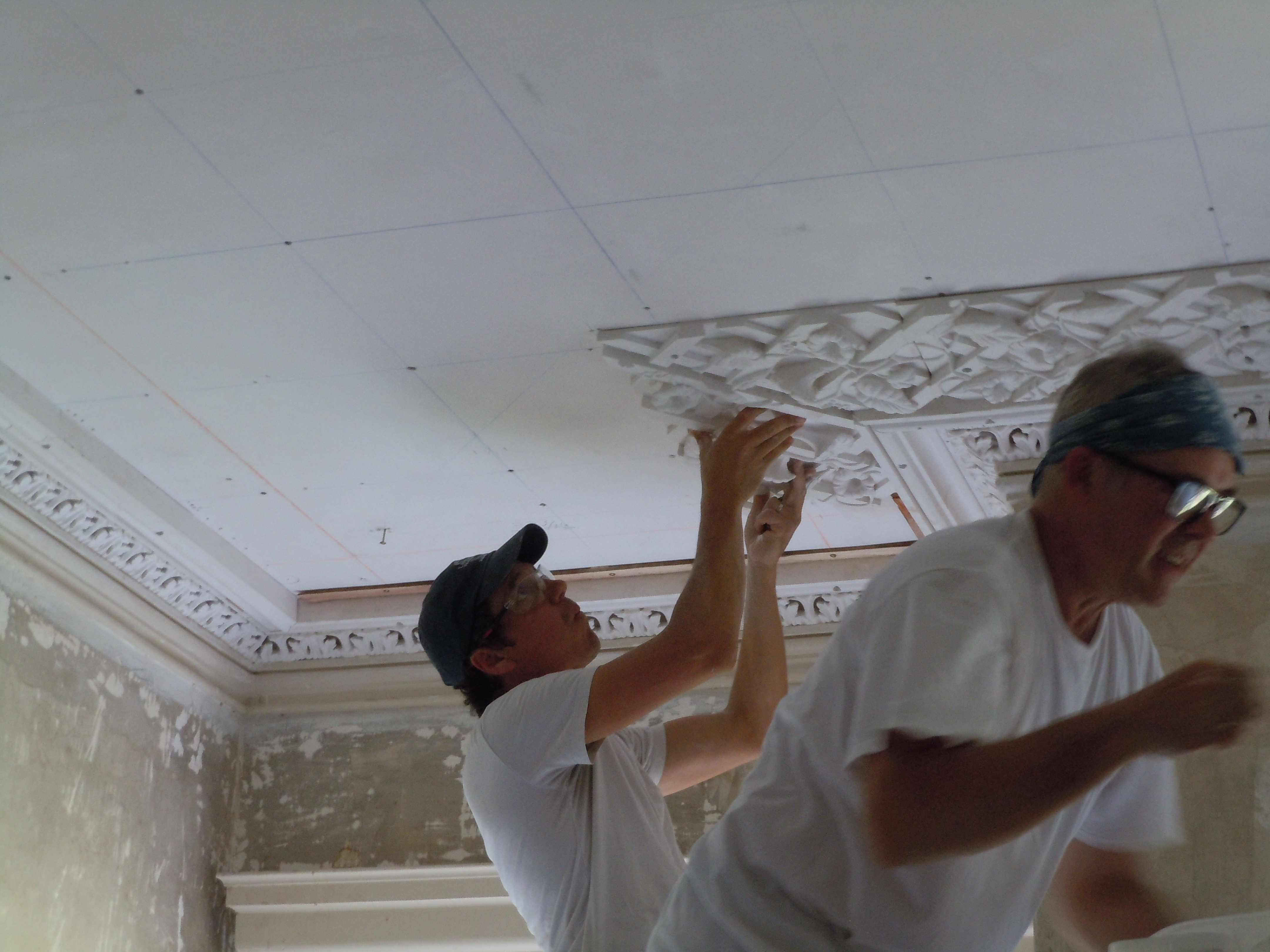 Greg Jacobs and Adam Chase of Landmark Preservation installing the perimeter plaster lattice in the front room.