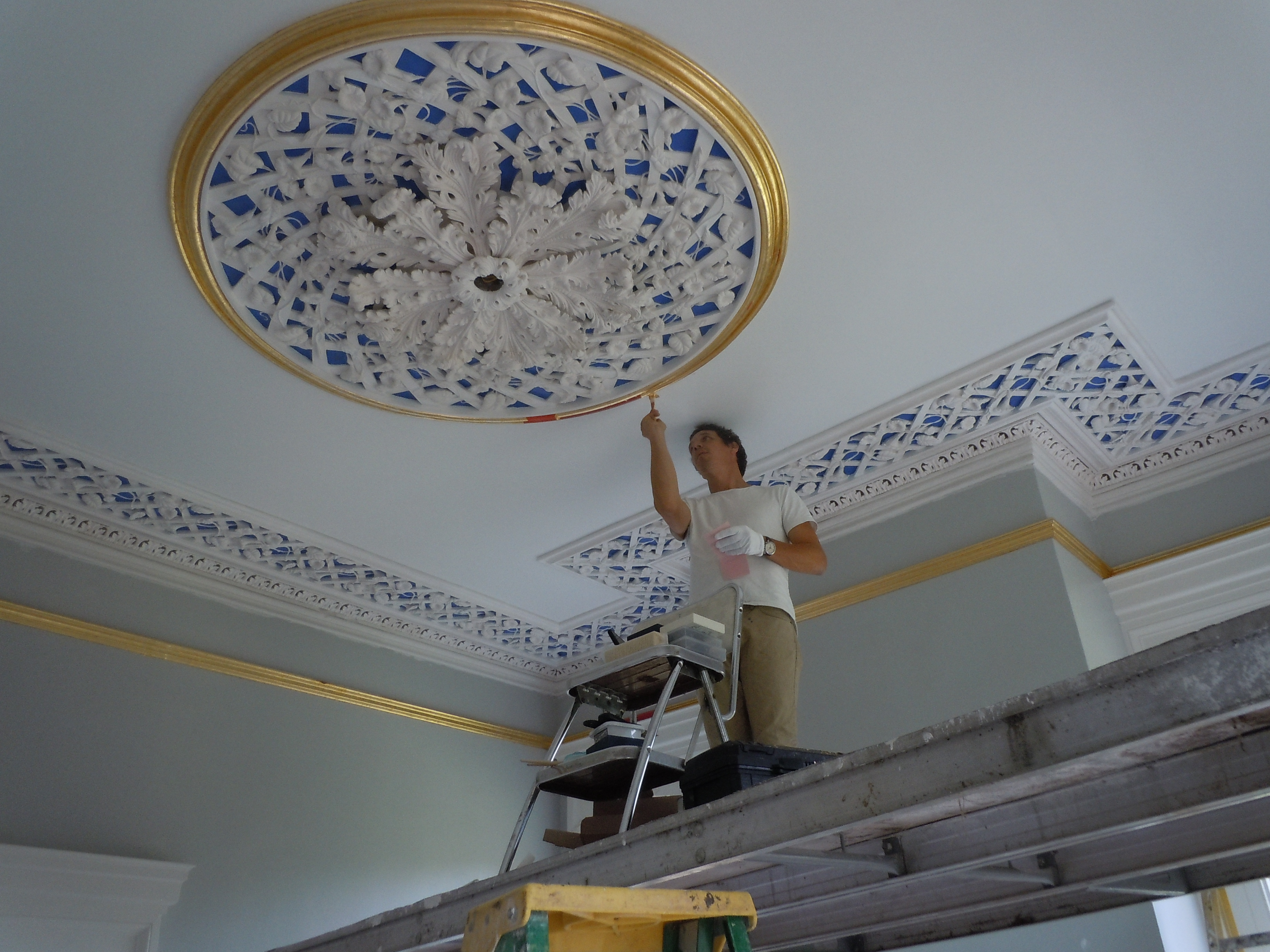 Greg Jacobs gilding the front room ceiling medallion.